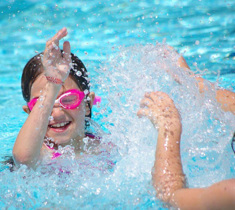 Petite fille jouant dans la piscine du camping dans le morbihan avec piscine couverte et Chauffée le Ty Nenez